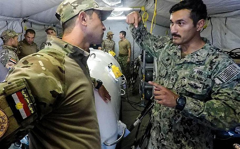Chief Petty Officer Eli Hernandez, a Navy corpsman, and an Egyptian servicemember discuss the physiological effects of diving during the Eagle Response 18 exercise in Egypt, Tuesday, July 24, 2018.   Chloe Morgan/U.S. Navy