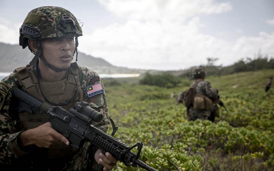 A Malaysian marine provides security on Pyramid Rock Beach during an amphibious-landing drill on Marine Corps Base Hawaii, Sunday, July 29, 2018.