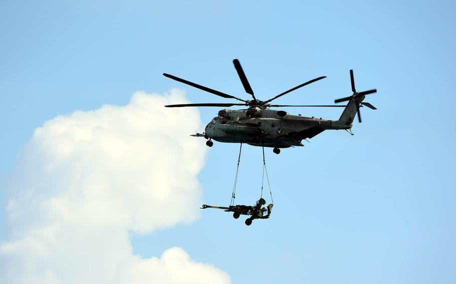 A Super Stallion airlifts a howitzer cannon during an amphibious-assault drill at Marine Corps Base Hawaii, Sunday, July 29, 2018.