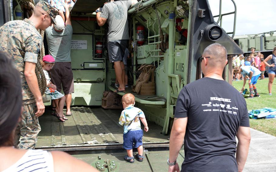 A young visitor inspects an amphibious-assault vehicle on display at Marine Corps Base Hawaii, Sunday, July 29, 2018.