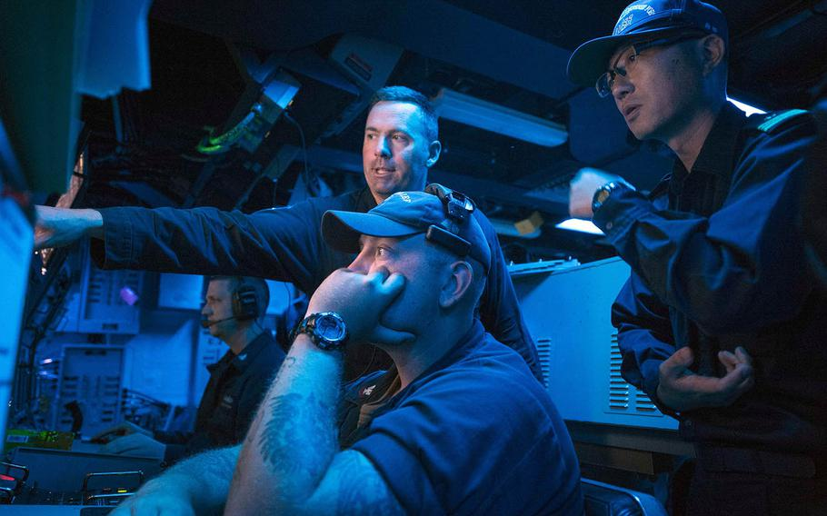 Lt. Cmdr. William Russell, commanding officer of the USS Chief, explains the ship's sonar capabilities to Lt. Cmdr. Akihiko Morita of the Japan Maritime Self-Defense Force, Monday, July 23, 2018.