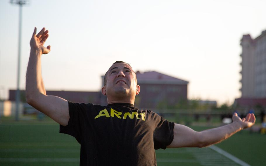 A soldier from the 1st Armored Combat Brigade, 3rd Infantry Division tosses a medicine ball over his head during a demo of the new Army Combat Fitness Test at Camp Humphreys, South Korea, Tuesday, July 31, 2018.