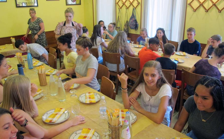 U.S.teenagers newly arrived to Italy with their parents during the summer PCS season await pizza near the end of a garrison-provided walking tour designed to acquaint them with the local culture.