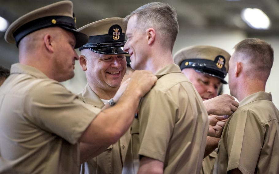 Senior chief petty officers receive their new rank insignia during a frocking ceremony aboard the aircraft carrier USS George H.W. Bush on June 15, 2018.