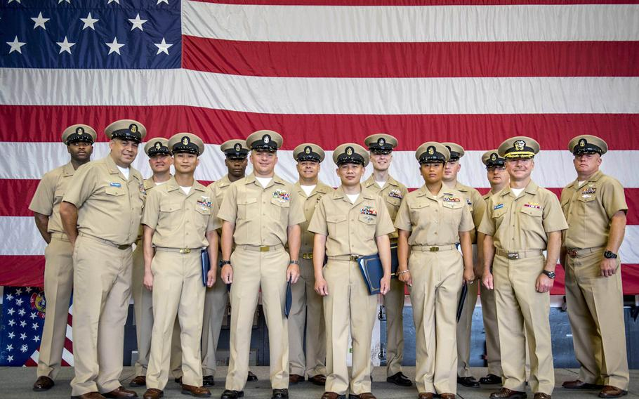 Newly frocked senior petty officers pose for a group shot after their frocking ceremony aboard the aircraft carrier USS George H.W. Bush, June 15, 2018. Chief petty officers willing to serve additional sea duty, take on tougher jobs and pursue promotions can apply for waivers that extend their Navy careers beyond the time when they would be involuntarily discharged.