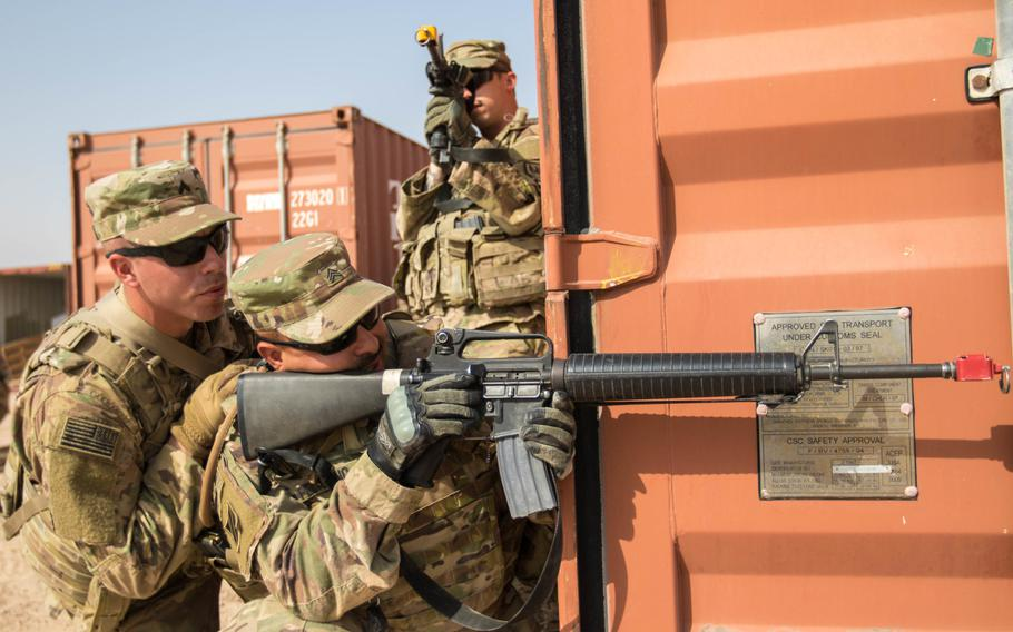 A squad leader communicates with his team leader behind cover during the STX at Camp Buehring, Kuwait. The soldiers are students in the Basic Leadership Course.