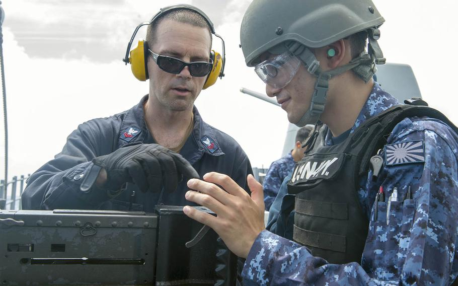 Petty Officer 2nd Class Matthew Spano instructs a member of the Japan Maritime Self-Defense Force member during a live-fire exercise aboard the guided-missile cruiser USS Antietam, Wednesday, Aug. 15, 2018.