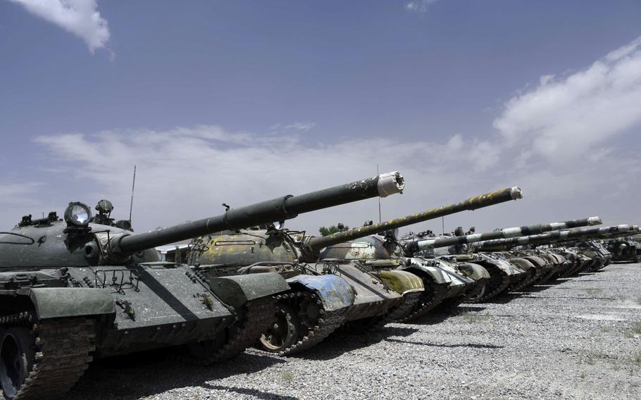 A row of T-55 and T-62 tanks with mismatched camoflauge patterns and rust spots stand in a lot at an Afghan army base on the eastern outskirts of Kabul on Saturday, June 23,2018.
