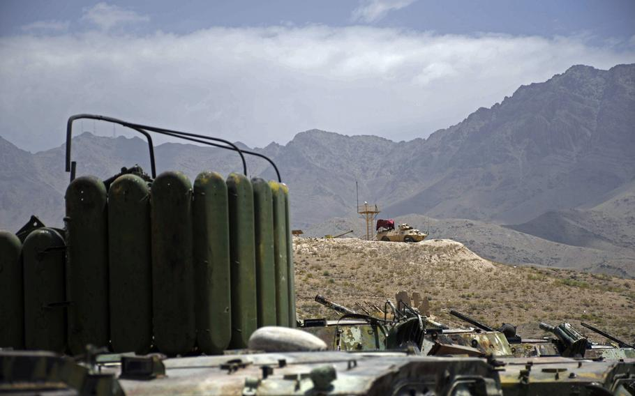 An Afghan mobile strike force vehicle stands watch on a ridge overlooking a lot full of obsolete Soviet-made tanks at an army base on the eastern outskirts of Kabul on Saturday, June 23, 2018.