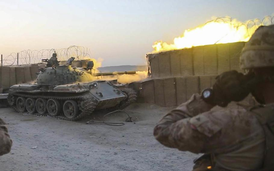 U.S. Marines with Task Force Southwest watch as an Afghan T-55 fires at an enemy position during an advisory mission at Camp Nolay in Sangin district, Helmand province, Wednesday, Aug. 8, 2018.