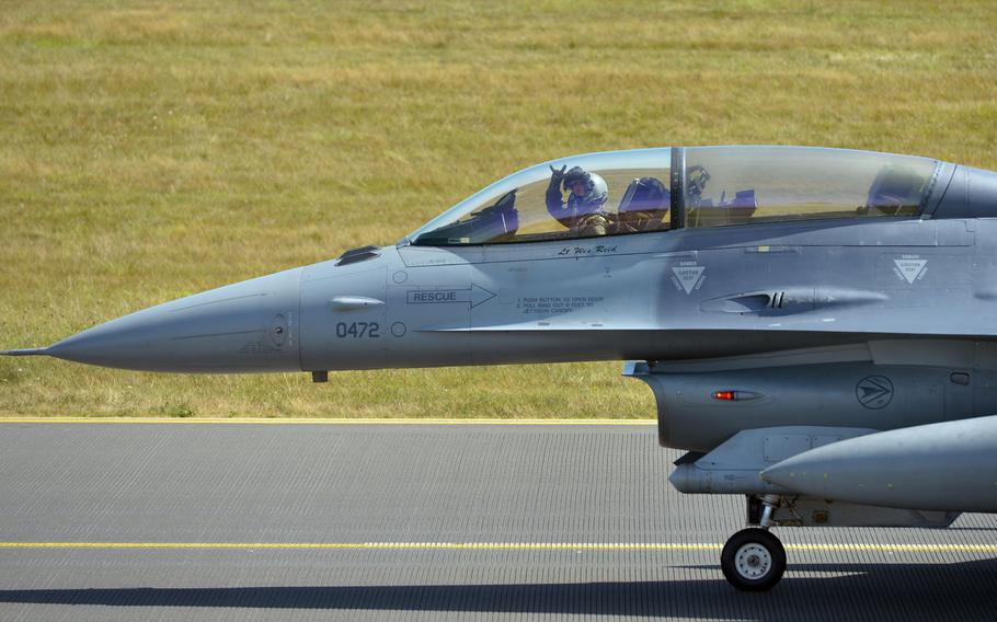 A F-16 Fighting Falcon pilot of the 480th Fighter Squadron waves to international photographers after landing at Spangdahlem Air Base, Germany, Thursday, Aug. 18, 2018. The photographers were at the base to photograph visiting F-22 Raptors.
