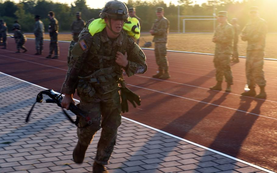 Sgt. Robert Lohr runs with a pack and rifle toward the finish line of the foot-march at the 2018 U.S. Army Europe Best Warrior Competition, Friday, Aug. 17, 2018, at Grafenwoehr, Germany.