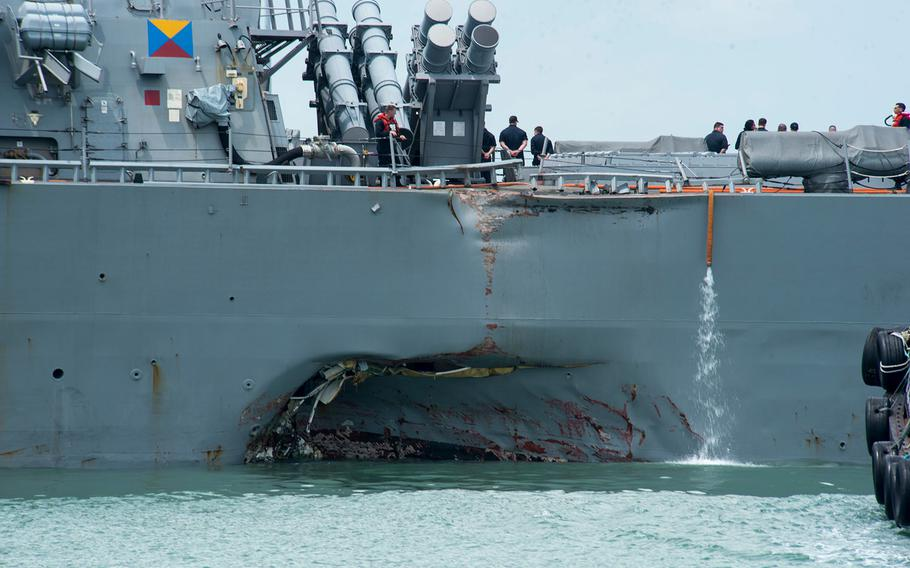 Damage to the portside is visible as the USS John S. McCain steers toward Changi Naval Base, Singapore, following a collision with a merchant vessel, Aug. 21, 2017.