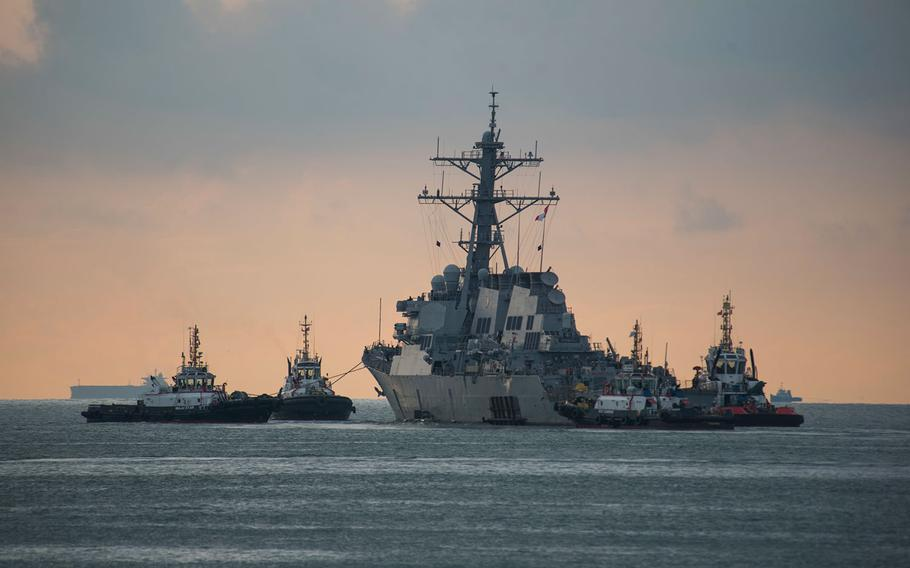 The USS John S. McCain is towed away from the pier at Changi Naval Base, Singapore, to meet the heavy lift transport vessel MV Treasure, Oct. 5, 2017.