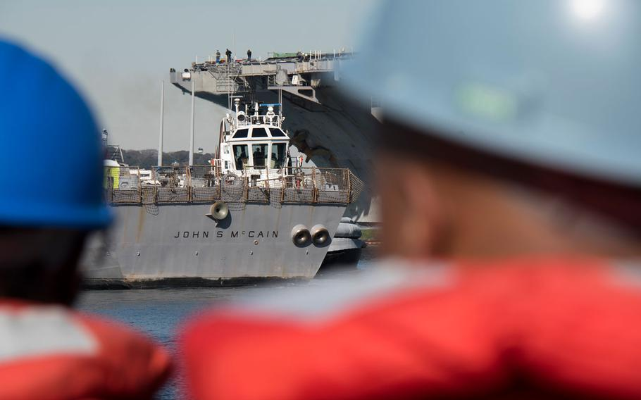The guided-missile destroyer USS John S. McCain is towed to the pier at Yokosuka Naval Base, Japan, the vessel's homeport.