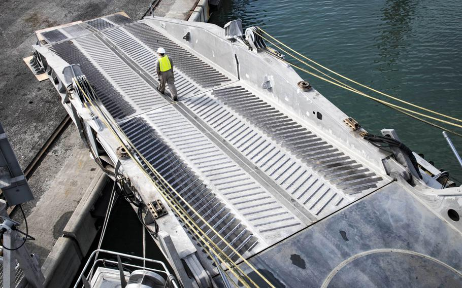 Civil service mariner 3rd Mate Christian Fitzgerald walks down the stern ramp of the expeditionary fast transport ship USNS Carson City in Poti, Georgia, Wednesday, Aug. 22, 2018.