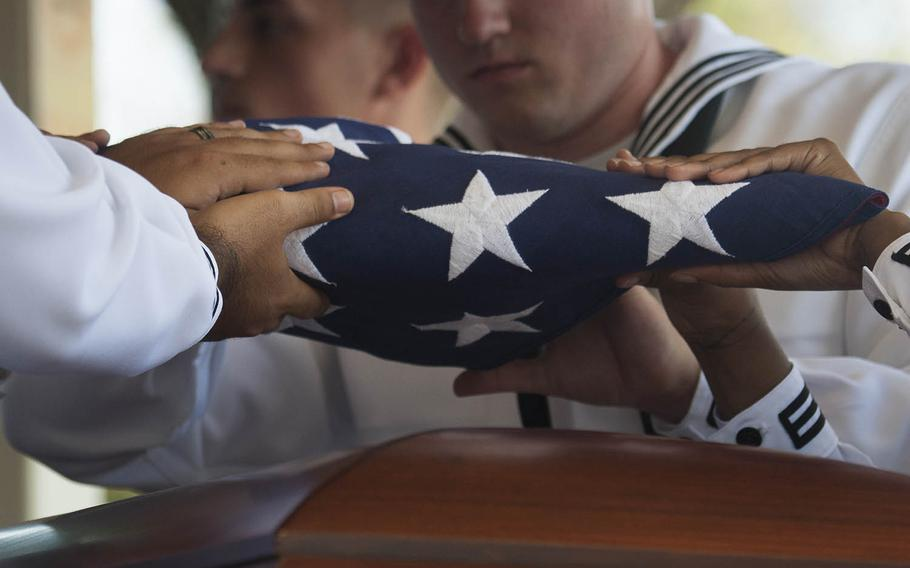 Navy Region Hawaii sailors fold a flag during the funeral of Petty Officer 1st Class Arthur Glenn, who died aboard the USS Oklahoma during the Pearl Harbor attack, at the National Memorial Cemetery of the Pacific, Hawaii, Aug. 21, 2018.