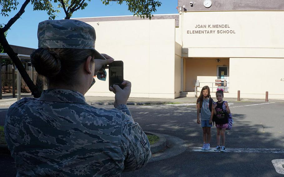 Air Force Staff Sgt. Jaimie Ropp captures a memory of her daughters, Laney and Kyndal Ropp, on the first day of school at Joan K. Mendel Elementary School at Yokota Air Base, Japan, Monday, Aug. 27, 2018.