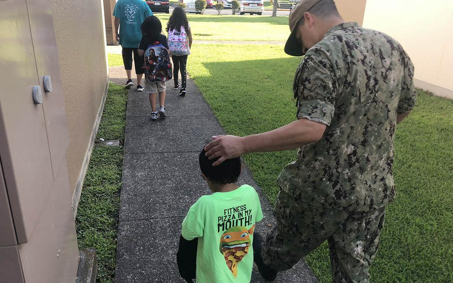 Chief Petty Officer Richard Fowler III walks with his son, Moises, 5, to Ikego Elementary School in Japan, Monday, Aug. 27, 2017. Moises will start kindergarten next week, but his siblings in second and fourth grades began Monday.