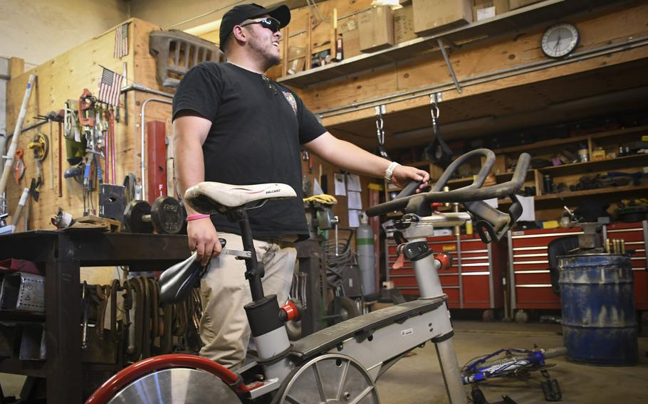 Don Baumgartner, director of Morale, Welfare and Readiness for Area Support Group-Afghanistan, picks up a spin bike he had repaired after finding parts at a scrapyard at Bagram Air Field, Afghanistan.