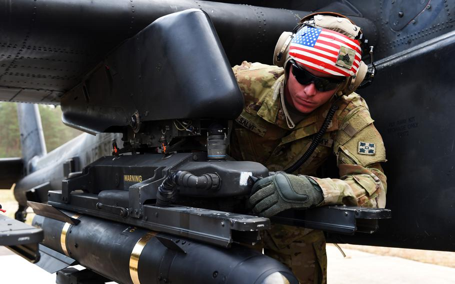 Sgt. Michael Salvi, an Apache helicopter electrician with the 6th Squadron, 17th Cavalry Regiment, 4th Infantry Division, checks the armaments of an AH-64D Apache during his squadron's first gunnery training since they arrived in Europe to support Operation Atlantic Resolve, at Grafenwoehr, Germany, Wednesday, Aug. 29, 2018.