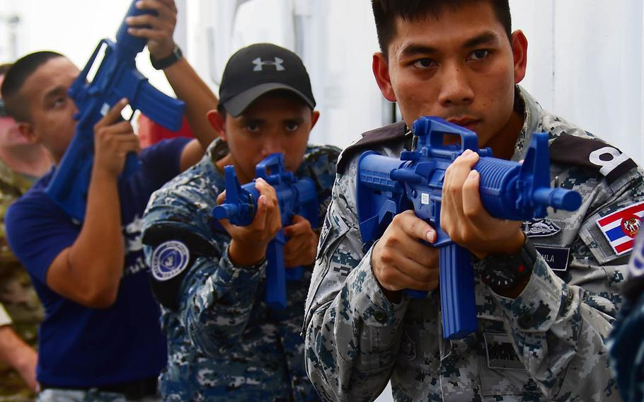 A Royal Thai Navy sailor, right, a Philippine coast guardsman, center, and a Royal Thai Marine police officer practice tactical procedures during Southeast Asia Cooperation and Training in Manila, Philippines, Wednesday, Aug. 29, 2018.