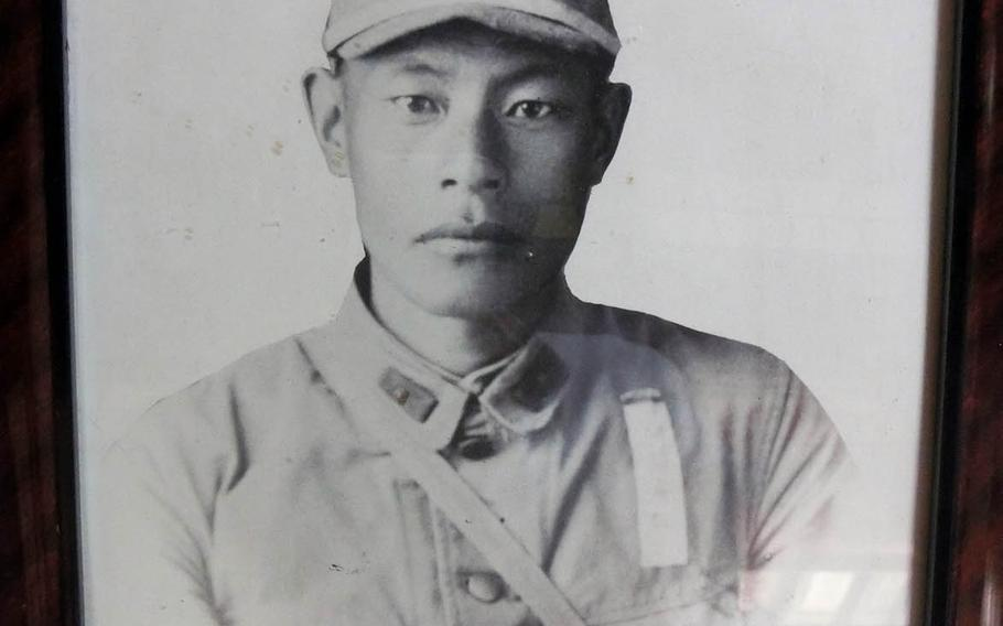 A framed photo of Japanese soldier Masamoto Abe, who died in New Guinea in 1944 at the age of 33.