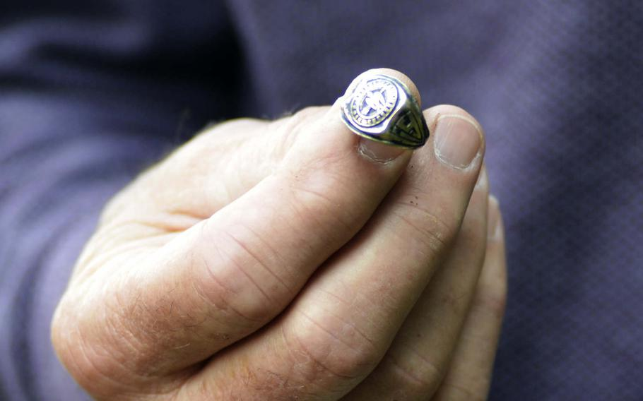 Ken Spatz holds his father's 1941 high school graduation ring near the crash site where he died during World War II in Ridgewell, England, Friday, Aug. 31, 2018. About a decade ago, British farmer Andy Cox found the ring near a disused World War II airfield in England.
