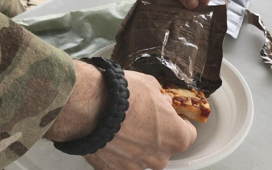 A U.S. servicemember pulls a Meal, Ready to Eat pepperoni pizza from its bag during a taste test of the new military ration at NATO headquarters in Kabul, Afghanistan, on Wednesday, July 4, 2018.