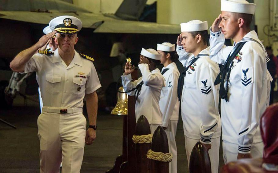 """Capt. Patrick """"Fin"""" Hannifin salutes during a change-of-command ceremony aboard the USS Ronald Reagan while at sea, Monday, Sept. 10, 2018."""