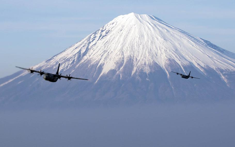 Two Air Force C-130J Super Hercules assigned to the 36th Airlift Squadron fly near Mount Fuji, Japan, March 26, 2018.