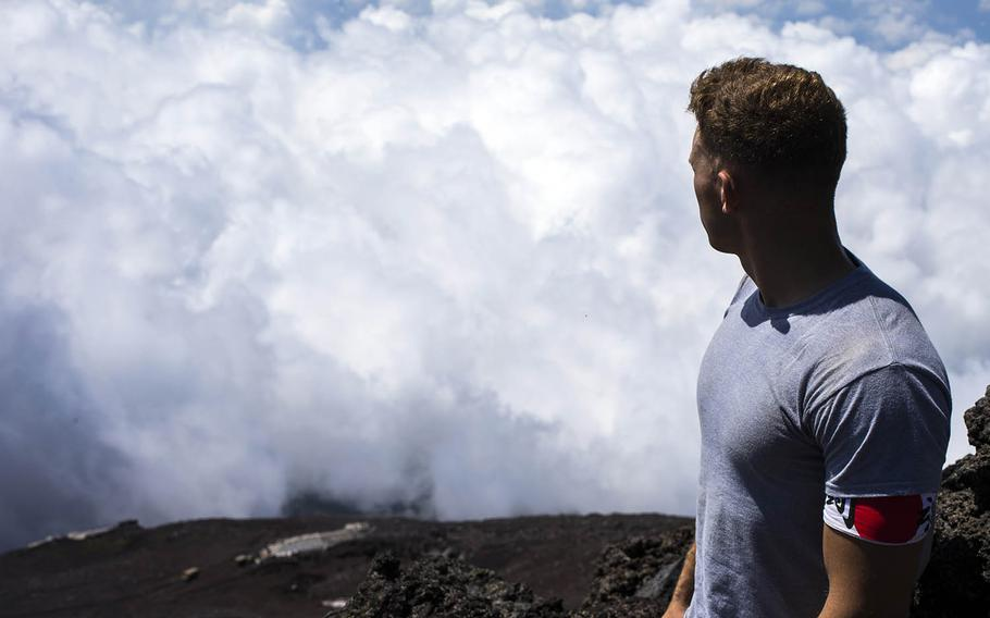 Cpl. Michael Onesty, an aviation precision measurement equipment technician with Marine Aviation Logistics Squadron 12, looks down from the summit of Mount Fuji, Aug. 2, 2018.