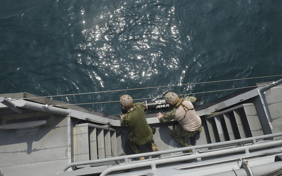 Two sailors launch a mine-hunting sonar device during Mine Countermeasures Exercise 18-3 in the Persian Gulf, Tuesday, Sept. 11, 2018.