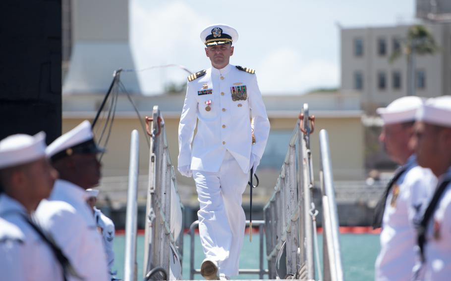 Cmdr. Dave Edgerton, outgoing commanding officer of Los Angles-class fast-attack submarine USS Columbia walks of the submarine after the change-of-command ceremony at Joint Base Pearl Harbor-Hickam, August 3, 2018.