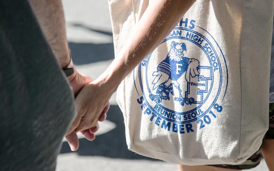 A woman carries a Seoul American High School reunion tote bag at Yongsan Garrison in Seoul, South Korea, Sunday, Sept. 9, 2018.