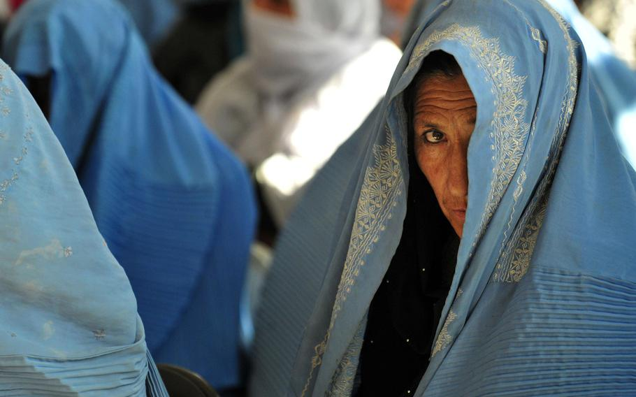 A woman peeks through her burqa to witness events at an International Women's Day celebration in Ghazni City, Afghanistan, March 8, 2011.