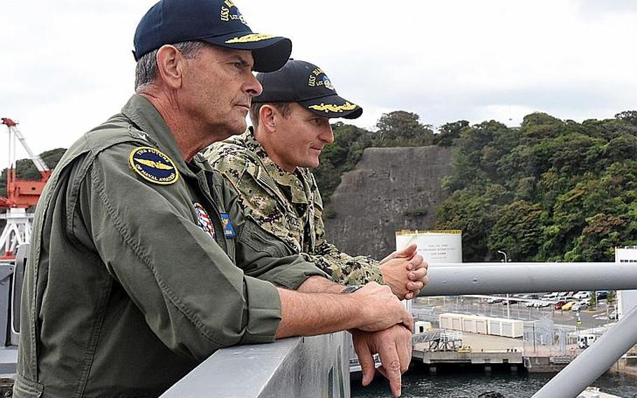 Vice Chief of Naval Operations Bill Moran speaks with Capt. Brett Crozier, commanding officer of the USS Blue Ridge, aboard the ship at Yokosuka Naval Base, Japan, Sept. 12, 2018.