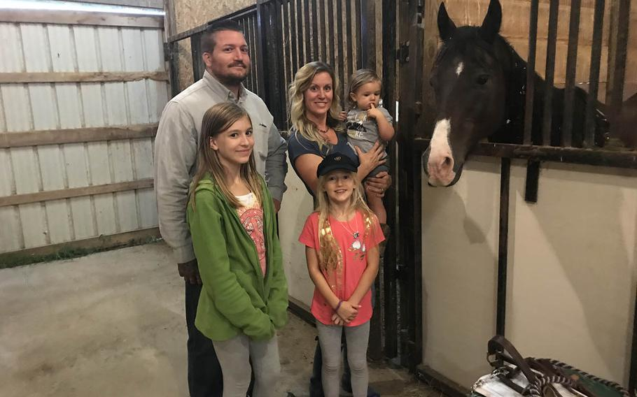 April Naiman, her spouse Kyle Naiman and their children, Olivia, 12, Lyla, 8, and Theodore, 2, pose with Big Ben, the horse April rode 15 years ago as a soldier with 1st Cavalry Division Horse Cavalry Detachment.