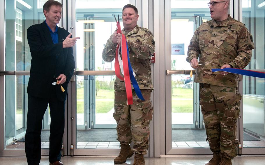 Stars and Stripes publisher Max Lederer, left, points at Col. Brent Coryell, commander of Defense Logistics Agency Pacific, during a ribbon-cutting ceremony for the newspaper's Korea headquarters at Camp Humphreys, Thursday, Sept. 20, 2018.