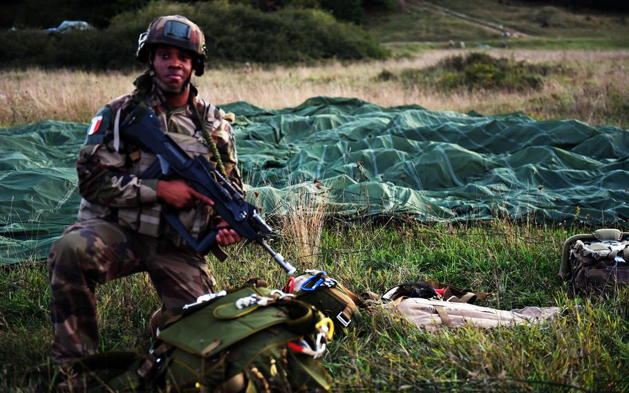 Cpl. Destine Peta, a French paratrooper, provides cover for U.S. troops after parachuting to the ground, during Exercise Saber Junction 18, at Hohenfels, Germany, Wednesday, Sept. 19, 2018.