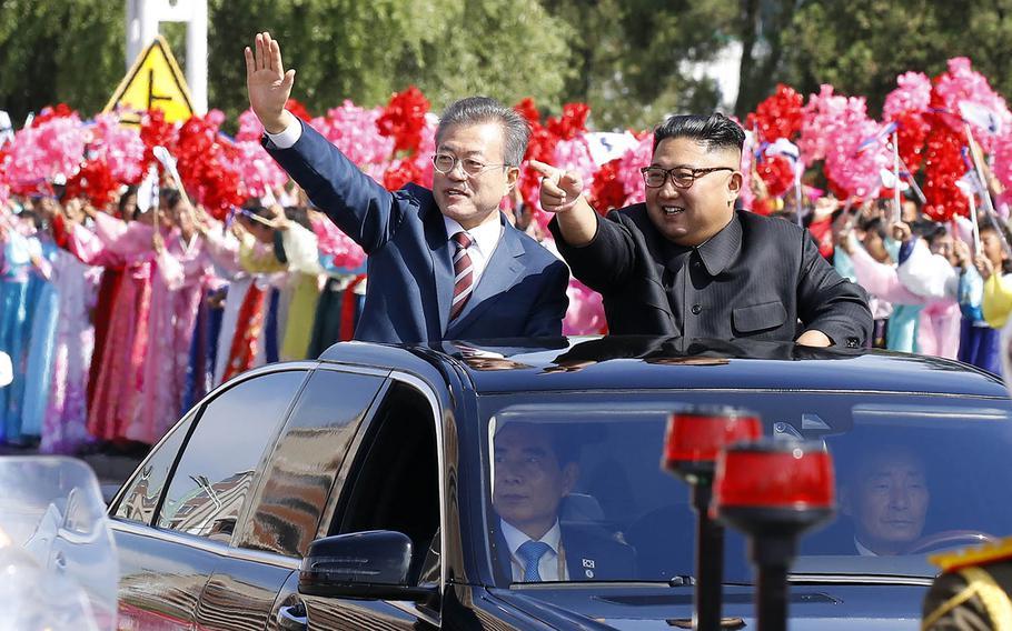 A vehicle carrying South Korean President Moon Jae-in, left, and North Korean leader Kim Jong Un makes its way through Pyongyang, North Korea, Tuesday, Sept. 18, 2018.