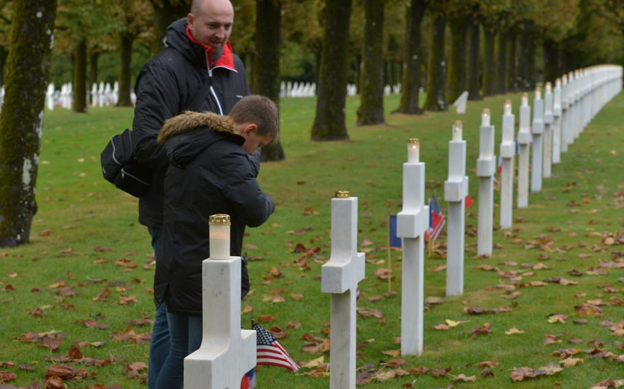 A Frenchman and his son light candles on a row of crosses at the Meuse-Argonne American Cemetery at Romagne-sous-Montfaucon, France, Sunday, Sept. 23, 2018. The American Battle Monuments Commission planned a luminary at the cemetery where candles were placed on its more than 14,000 graves. But wind and heavy rains cancelled the event. The ceremony marking the centennial of the Meuse-Argonne Offensive was held in the cemetery's chapel.