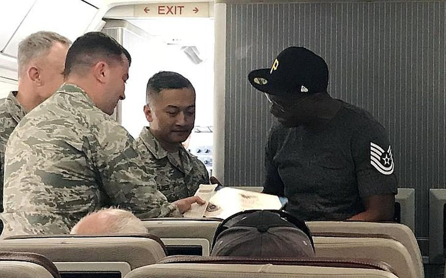 Terry White receives a surprise promotion to technical sergeant aboard a Patriot Express flight before leaving Osan Air Base, South Korea, Thursday, Sept. 27, 2018.