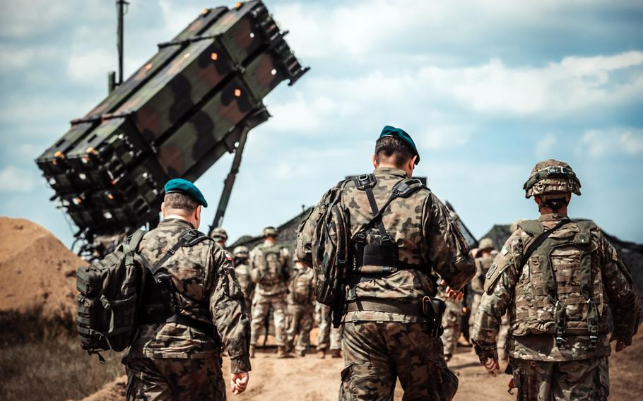 Servicemembers from the U.S. Army and the Polish Land Forces walk to the site of the new Patriot missile system for near Drawsko Pomorskie, Poland, June 4, 2018.