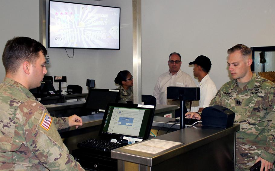 Pvt. Daniel Wilson, 212th Combat Support Hospital, accepts payment from Cpt. Timothy Brocks, 10th Army Air and Missile Defense Command, at the Defender Cafe at Rhine Ordnance Barracks, Kaiserslautern, Germany. The dining facility is one of 14 in Europe that now offer credit and debit card payment.