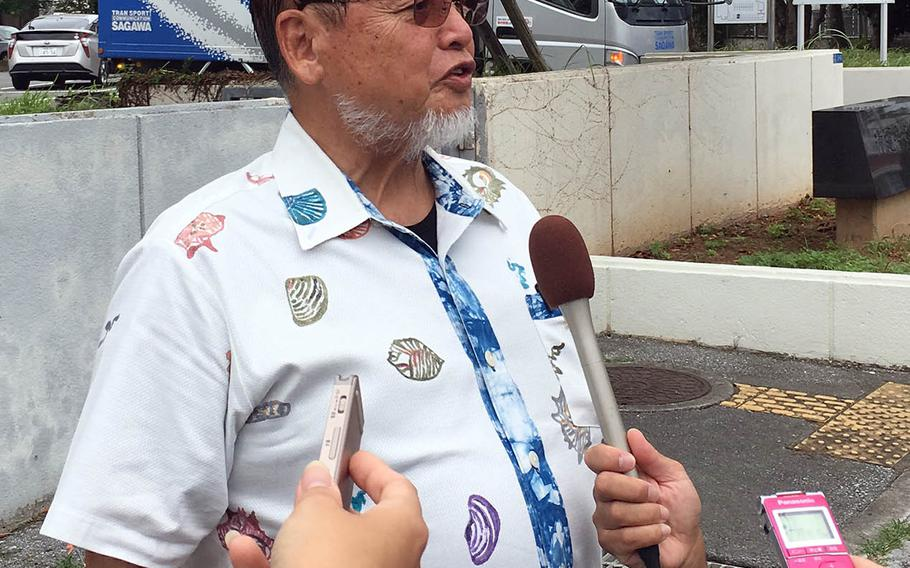 Kenei Yamashiro, a leader of a group seeking $10 million in damages over noise from Marine Corps Air Station Futenma, speaks to reporters near Naha District Court, Friday, Sept. 28, 2018.