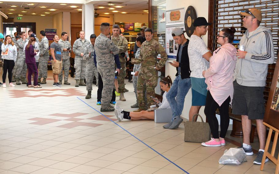 Airmen at Aviano Air Base's military clothing shop wait for the store to open so they can purchase their new Operational Camouflage Pattern uniforms, Monday, Oct. 1, 2018.