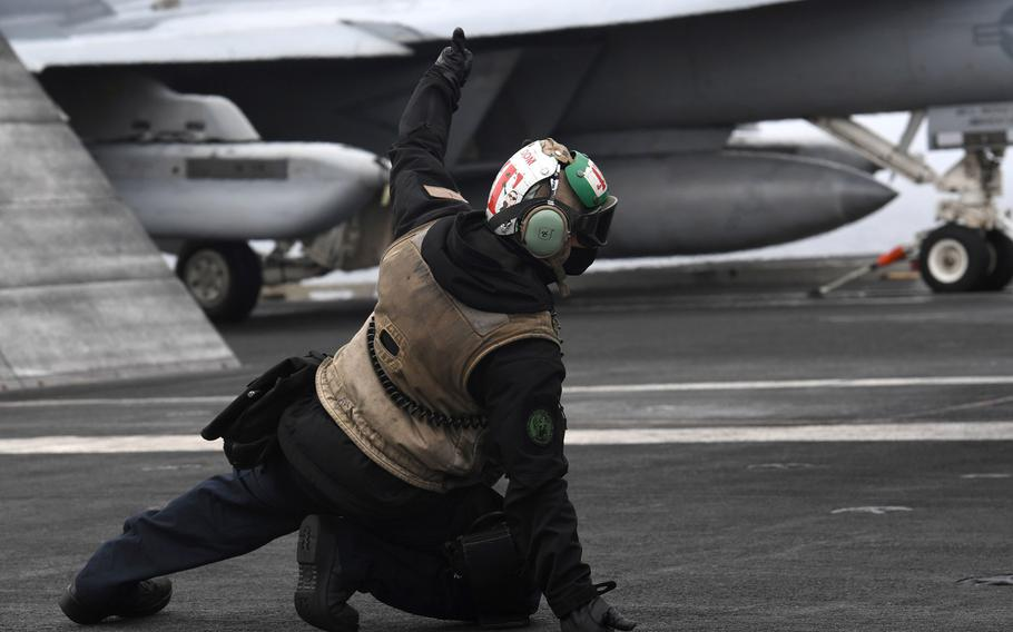 Aviation Electronics Technician 2nd Class Andrew Valera, assigned to the Sunliners of Strike Fighter Squadron 81, signals to launch an F/A-18E Super Hornet from the aircraft carrier USS Harry S. Truman, Sept. 26, 2018.