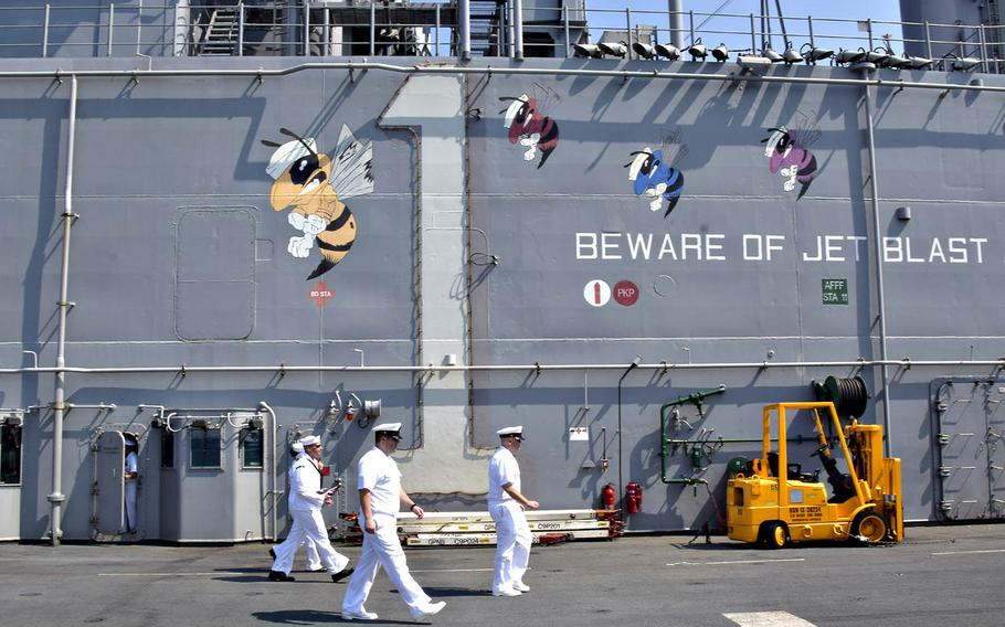 Sailors aboard the USS Wasp prepare to man the rails as the amphibious-assault ship arrives in Singapore, Tuesday, Oct. 2, 2018.