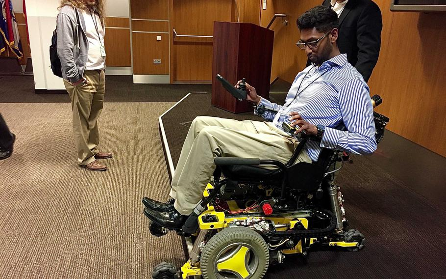 Sivashankar Sivakanthan, a student and graduate researcher with the Human Engineering Research Laboratories program at the University of Pittsburgh, shows how a MEBot reconfigures its wheels to negotiate a curb on Wednesday Oct. 3, in Wiesbaden, Germany. The MEBot, a new type of robotic wheelchair, promises greater independence and mobility for paralyzed veterans.